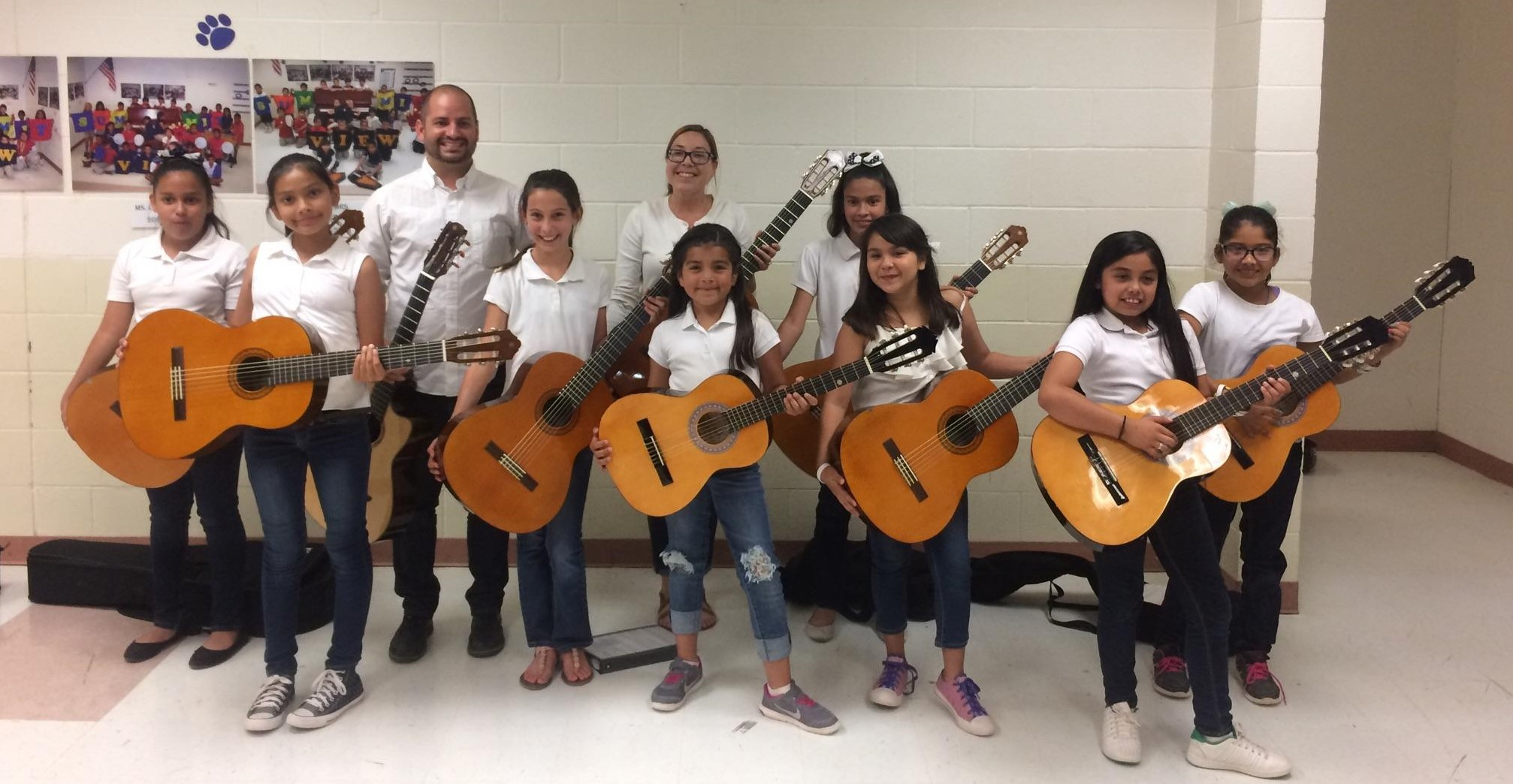 Lead Guitar elementary students get ready to go on stage holding guitars