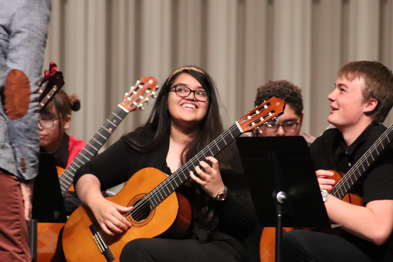 Lead Guitar high school ensemble student smiles during a UArizona performance